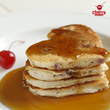 Stack of three heart shaped cherry pancakes drizzled in syrup