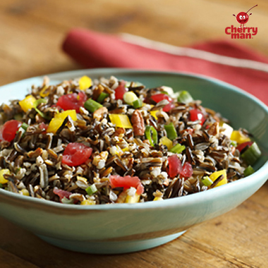 Wild rice salad in blue dish with maraschino cherries